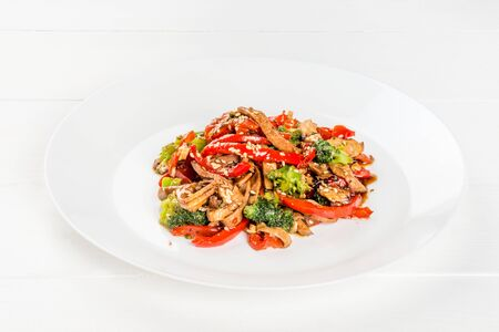 Salad with meat and vegetables sprinkled with sesame seeds shot on a white plate Stock Photo