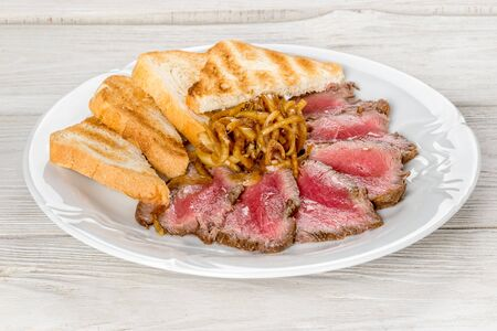 Roast beef with toast on a white plate. Close-up shot on a wooden white background. Stock Photo