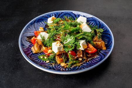 Close-up shot of a salad with eggplant and fresh herbs on a black background Stock Photo