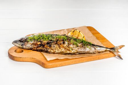 Grilled mackerel served with lemon served on a wooden board shot on a white background