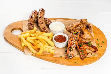 Beer set made of sausage, ribs, grilled wings. Close-up shot on a wooden board.