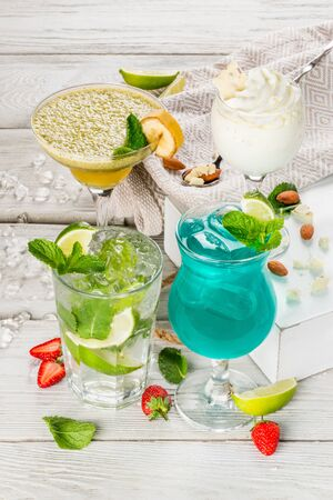 Smoothie banana, bounty, mojito, different cocktails on wooden background close-up