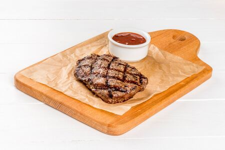 Close-up shot of beef steak on a wooden board with sauce