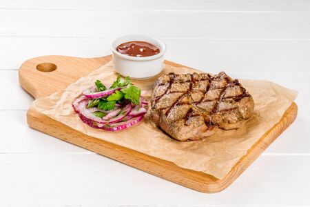 Grilled pork steak with sauce on a wooden board close-up