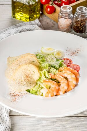 Caesar with shrimp in a white plate shot in decor