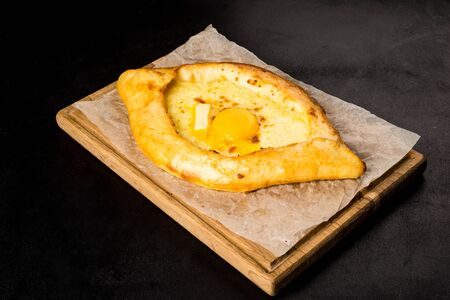 Khachapuri with egg and butter on a wooden board black background Stock Photo