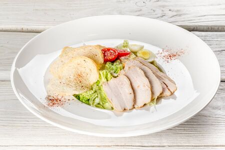 Close-up salad with caesar and chicken on a white plate