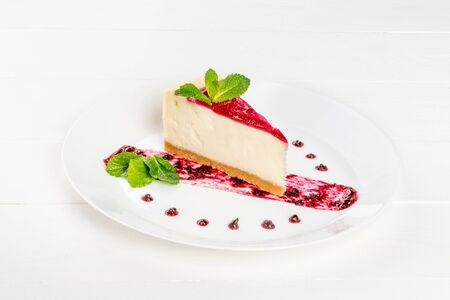 A piece of cheesecake decorated with jam decorated with mint leaves