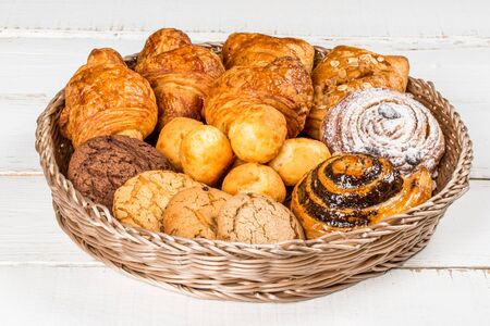 Croissant, cookies, rolls in a basket shot on a white wooden background shot close-up Stock Photo