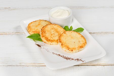 Cheesecakes with sour cream decorated with mint leaves on a white plate Stock Photo