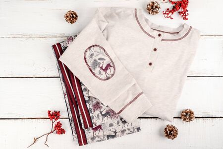 Pajamas with a pattern on the sleeve shot in the decor on a white wooden background