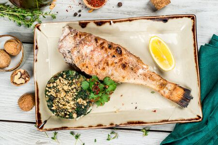 Grilled perch on a beautiful plate with lemon and salad