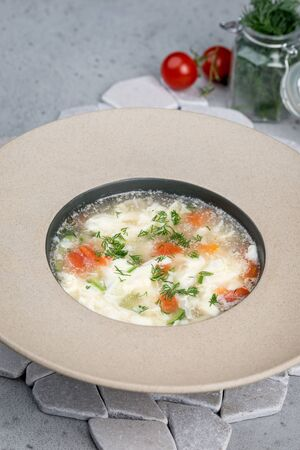 Soup with egg and fresh herbs in a deep plate