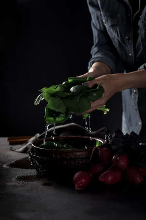 Female hands tossing vegetables in a bowl of water 版權商用圖片