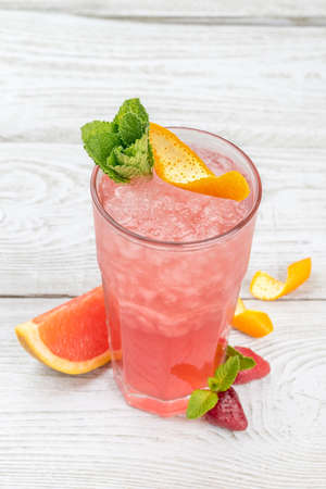 Grapefruit lemonade with ice in a glass cup. Close-up shot