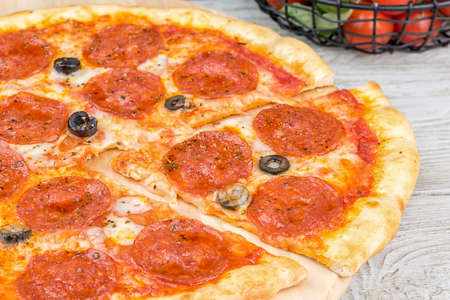 Pepperoni pizza with sliced one slice on a wooden board. Close-up shot