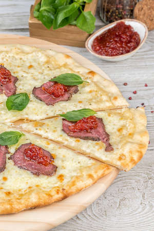 Pizza with roast beef cut one slice on a wooden board. Close-up shot
