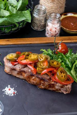 Grilled steak served on a black slate board. Close-up shot Imagens