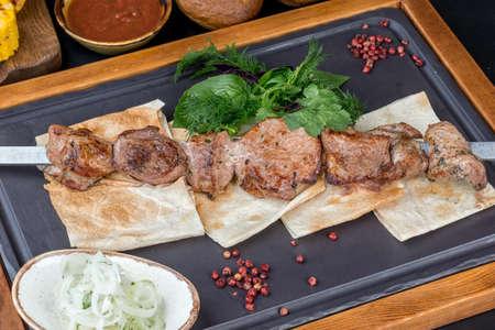 One kebab with pita bread on a black, slate board. Close-up shot