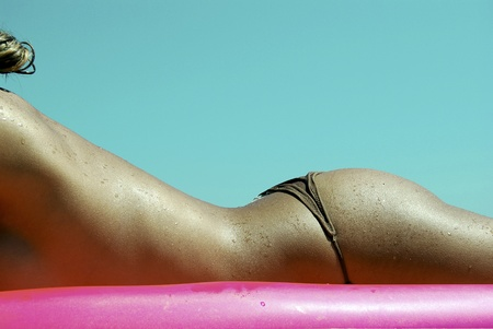 Photography. bronzed and beautiful woman on the beach. girl in bikini sunbathing