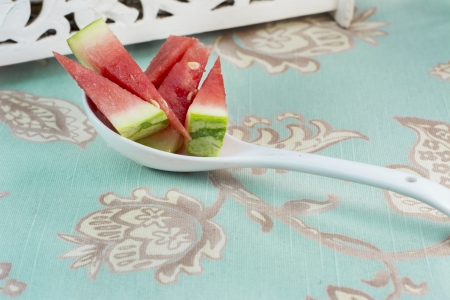 Vertical image, chunks of watermelon in white spoon on vintage background, blue and flowery photo