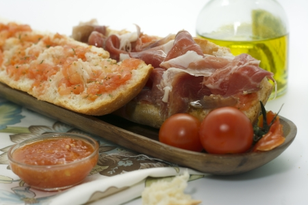 baguette with jamon iberico, tomato on wooden board