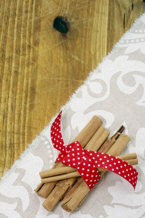 Cinnamon sticks, wrapped in red ribbon on cloth, and rustic wood. Vertical image photo