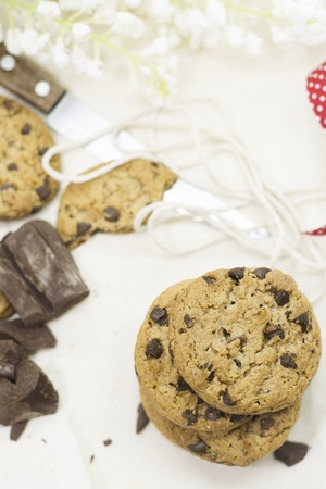 Cookies, chocolate chips on red ribbon rustic tablecloth and flowers photo