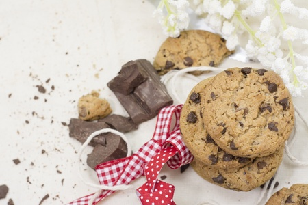 Cookies, chocolate chips on red ribbon rustic tablecloth and flowers Stock Photo - 21927684