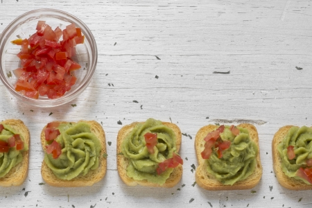 Mini-toast, decorated with guacamole, chopped tomato, white wooden background