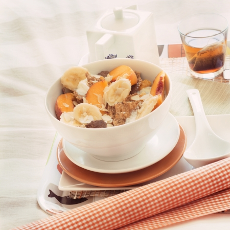 Breakfast in bed tray cereal, peach and banana, yogurt and tea, warm orange color. Square image