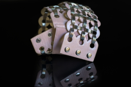 pink leather belt with metal clasps on black background