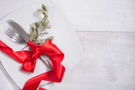 Festive table setting and decoration with red ribbon, on white wood photo