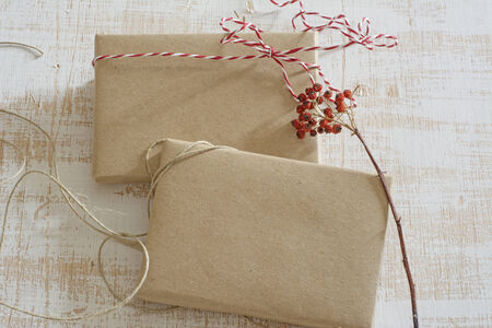 gift box wrapped in recycled paper, with ribbon bow,  with ribbon rustic, red and white  photo