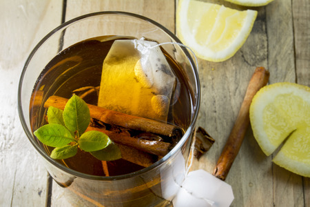 healthy cup of hot tea on wooden background, lemon and cinnamon  Stock Photo