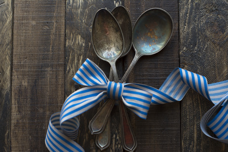 silver ribbon: Vintage metal spoons on wooden table close-up