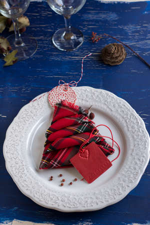 Christmas Dinner rustic, white plate, and napkin red boxes in the shape of tree, Blue background photo