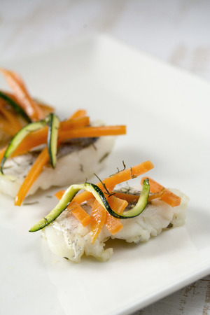 hake: Hake in pieces grilled with vegetables on white plate Stock Photo