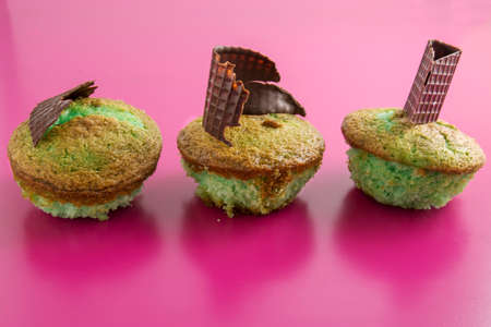 caloric: Mint tasty cupcakes on pink background, decorated with chocolate shapes Stock Photo