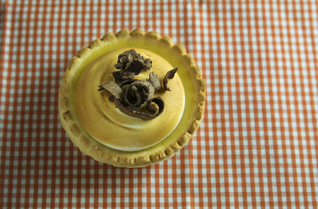 chocolate curls: Lemon cake and Italian meringue, decorated with chocolate curls on orange checkered tablecloth