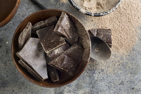 pieces: dark chocolate chunks in wooden bowl, on oak table Stock Photo