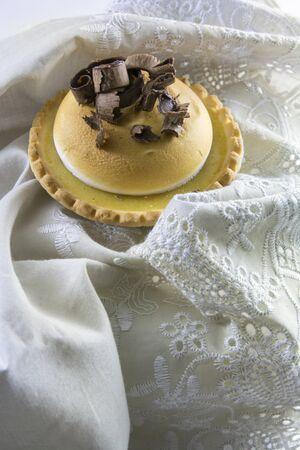 chocolate curls: Lemon cake and Italian meringue, decorated with chocolate curls on orange wood background