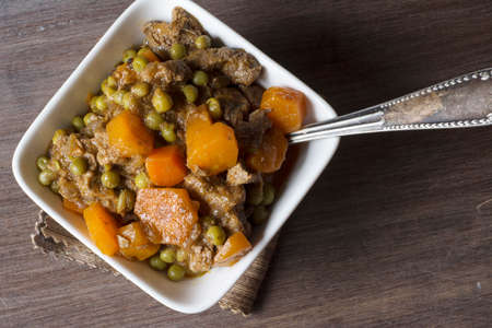 irish easter: hot beef stew with carrots and tomato sauce, on wooden background