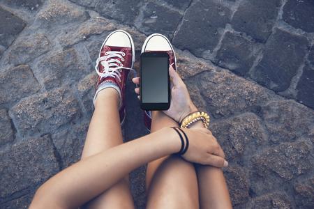 terra arrendada: menina do adolescente senta-se com telefone celular na mão, no antigo piso de pedra