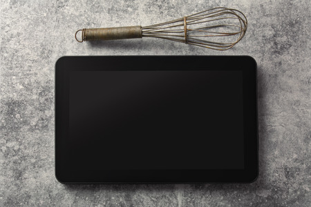 grunge silverware: Digital tablet, with whisk and antique silverware, on grunge background