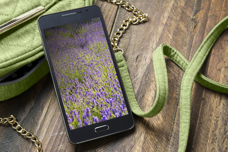 Mobile phone with background of flowers and hand bag woman