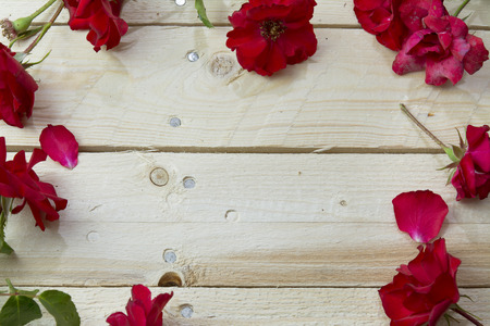 木製の背景に赤いバラのフレーム