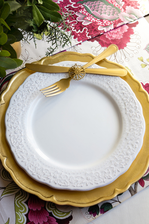 place setting: christmas place setting, table ready for lunch, on golden plates and white patterned background in flowers