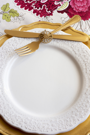 formal place setting: christmas place setting, table ready for lunch, on golden plates and white patterned background in flowers