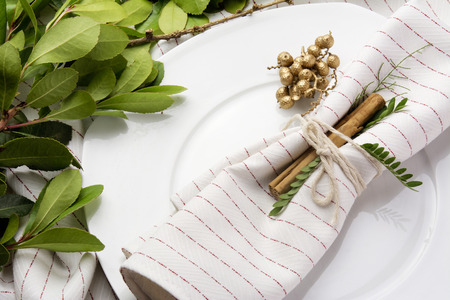 place setting: elegant place setting white and gold, with garland of green leaves Stock Photo